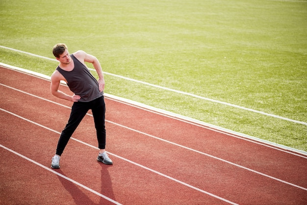 Porträt des sportlers das trainieren auf rennstrecke tuend Kostenlose Fotos