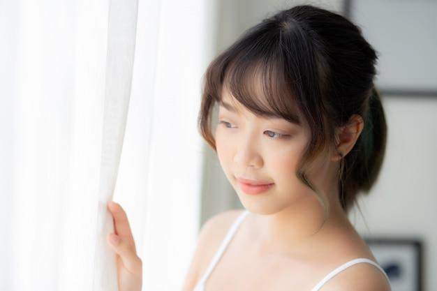 Porträt des stehenden blickes der schönen jungen asiatischen frau am fenster Premium Fotos
