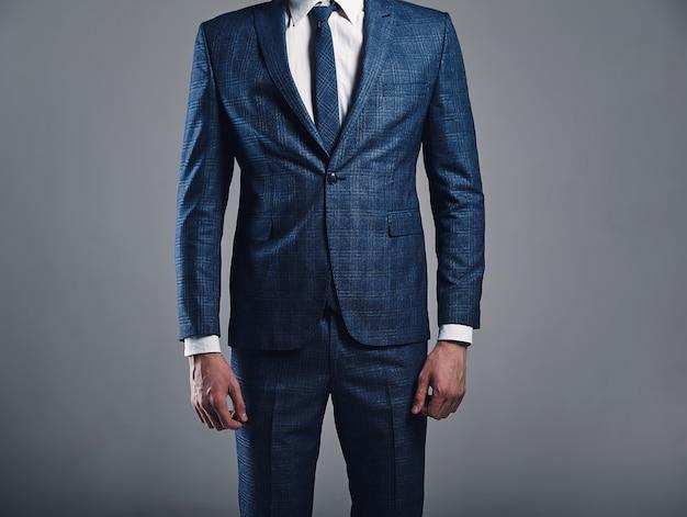 Porträt des stilvollen geschäftsmannmodells der hübschen mode kleidete im eleganten blauen anzug an, der auf grauem hintergrund im studio aufwirft Kostenlose Fotos