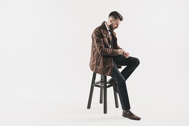Porträt des stilvollen hübschen jungen mannes, der im studio gegen weiß sitzt. mann trägt jacke Kostenlose Fotos
