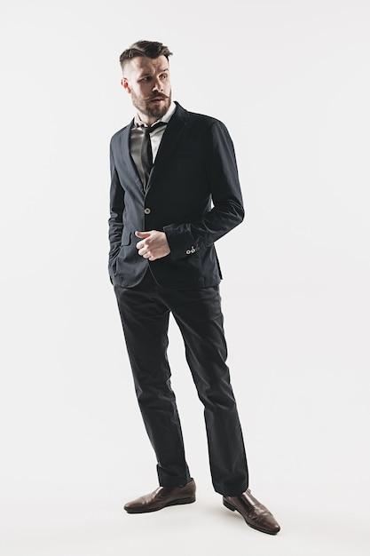 Porträt des stilvollen hübschen jungen mannes, der im studio gegen weiß steht. mann trägt jacke Kostenlose Fotos