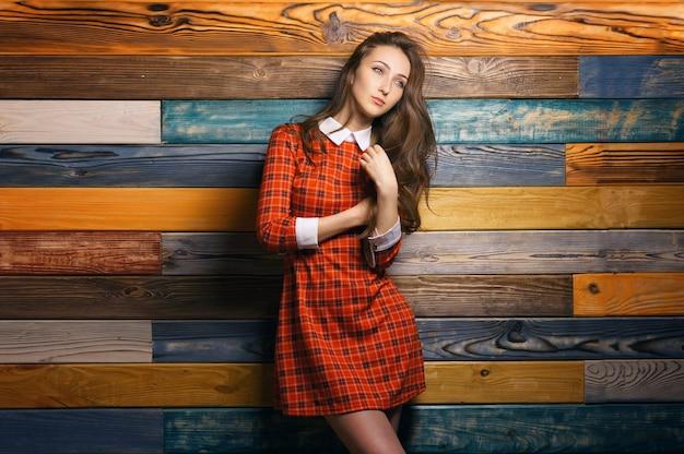 Porträt des studenten der jungen hipster-frau im roten kleid auf buntem hölzernem wandhintergrund Premium Fotos