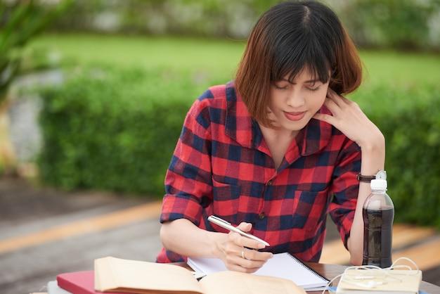 Porträt des studenten draußen beschäftigt mit hausarbeit im campus Kostenlose Fotos