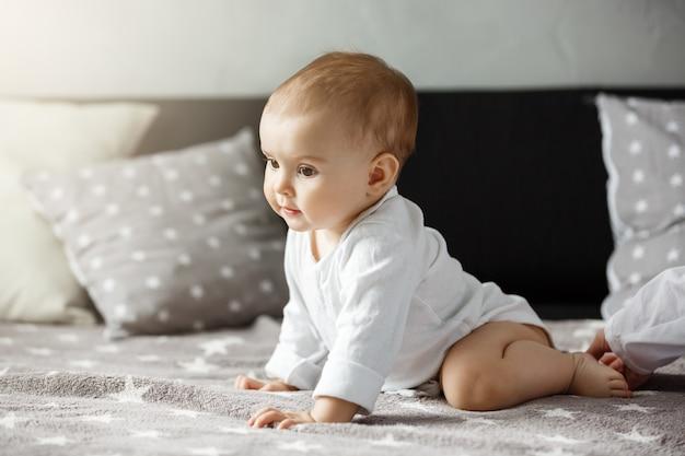 Porträt des süßen babys, das auf gemütlichem bett sitzt. kind schaut zur seite und kriecht glücklich zur mutter. familien-, mutterschaftskonzept. Kostenlose Fotos