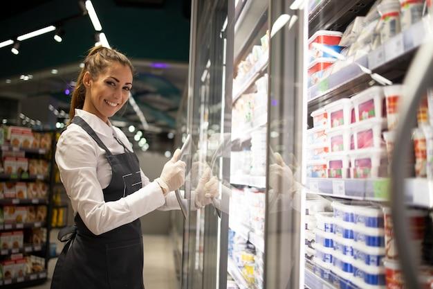 Porträt des supermarktarbeiters, der mit dem gefrierschrank mit essen steht Kostenlose Fotos