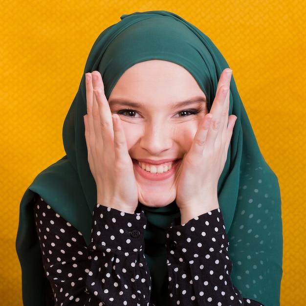 Porträt des tragenden hijab der glücklichen moslemischen frau, das kamera betrachtet Kostenlose Fotos