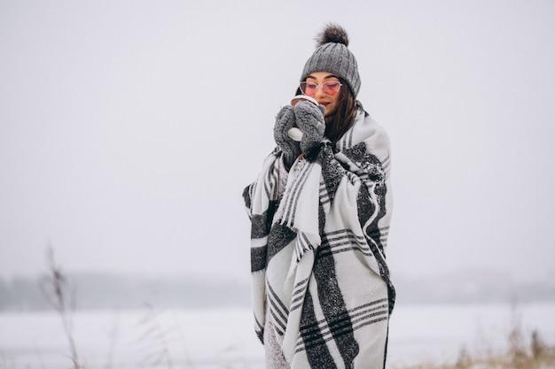 Porträt des trinkenden kaffees der jungen frau in einem winterpark Kostenlose Fotos