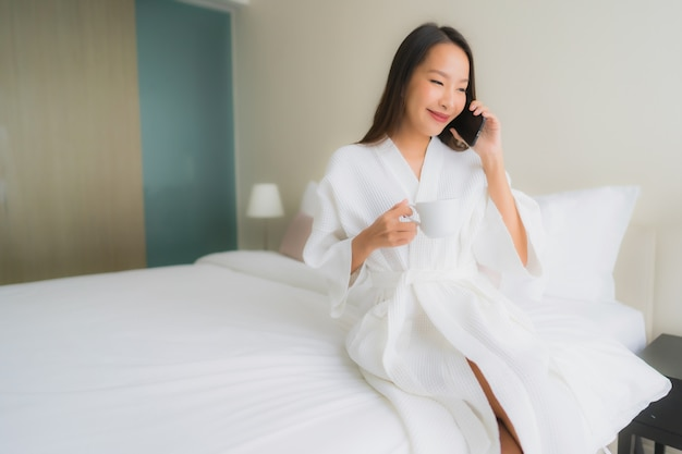 Porträt des trinkenden kaffees der schönen jungen asiatischen frau und der unterhaltung am telefon Kostenlose Fotos