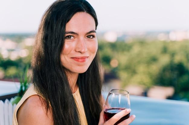 Porträt des trinkenden weins der frau auf der dachspitze Kostenlose Fotos