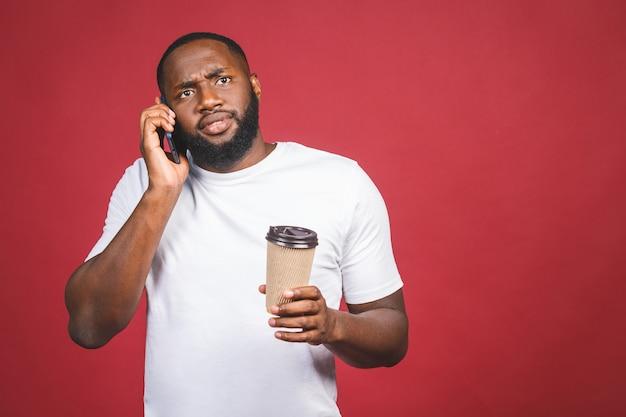 Porträt des überraschten gutaussehenden afroamerikanischen mannes mit handy und kaffeetasse zum mitnehmen. isoliert über rotem hintergrund. Premium Fotos