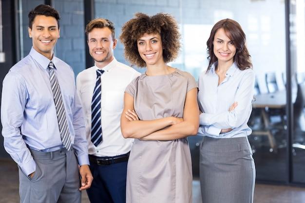 Porträt des überzeugten geschäftsteams, das im büro mit ihren händen gekreuzt steht Premium Fotos
