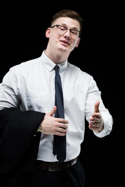 Porträt des überzeugten hübschen ehrgeizigen lächelnden eleganten verantwortlichen geschäftsmannes mit dem daumen oben auf schwarzem hintergrund Premium Fotos