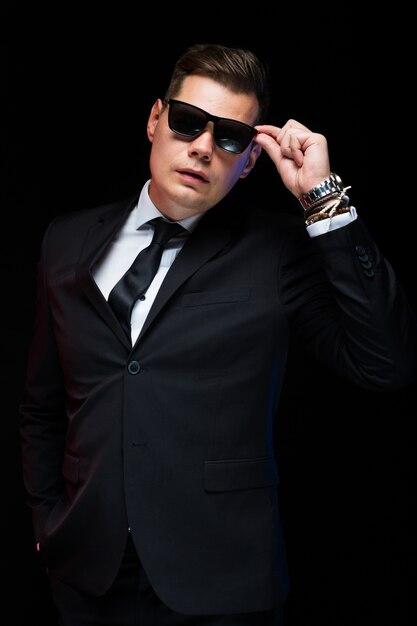 Porträt des überzeugten hübschen eleganten geschäftsmannes in der sonnenbrille auf schwarzem Premium Fotos