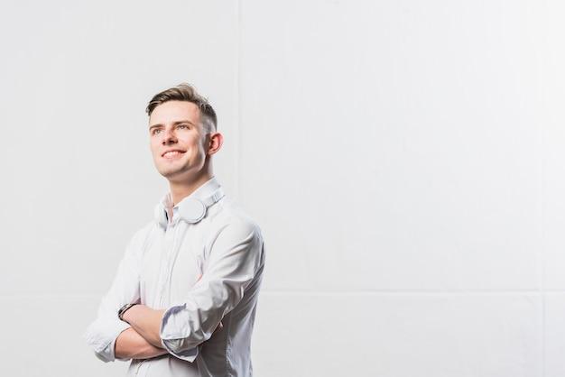 Porträt des überzeugten jungen mannes mit kopfhörer um seinen hals, der mit seinen armen steht, kreuzte gegen weiße wand Kostenlose Fotos