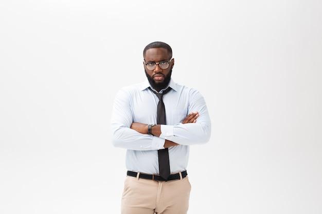 Porträt des verärgerten oder gestörten jungen afroamerikanermannes im weißen polohemd, welches die kamera mit missfallenem ausdruck betrachtet. Premium Fotos