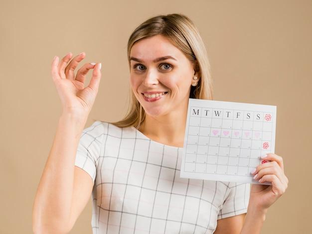 Porträt des weiblichen haltenen menstruationskalenders des smiley Kostenlose Fotos