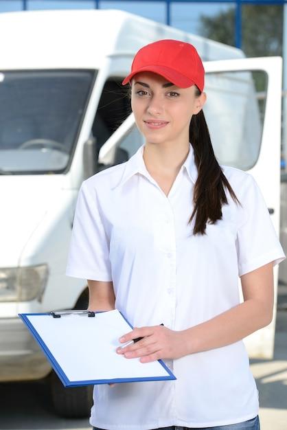Porträt des weiblichen lieferungsfahrers mit klemmbrett und kasten. Premium Fotos