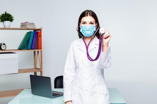 Porträt des weiblichen medizintherapeutenarztes, der mit gekreuzten händen auf ihrer brust hält, die stethoskop im amt hält. medizinische hilfe oder versicherungskonzept. Kostenlose Fotos