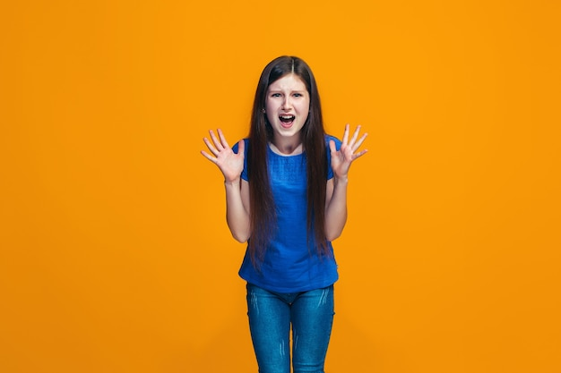 Porträt des wütenden jugendlich mädchens auf einem orange studio Kostenlose Fotos