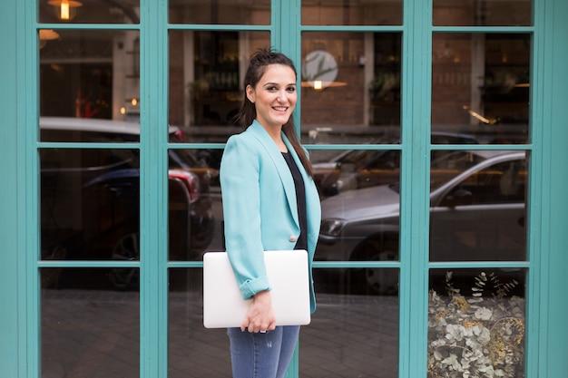 Porträt draußen der jungen glücklichen bloggerfrau mit modernem laptop. glasfenster hintergrund. freizeitkleidung tragen. spaß und lebensstil Premium Fotos