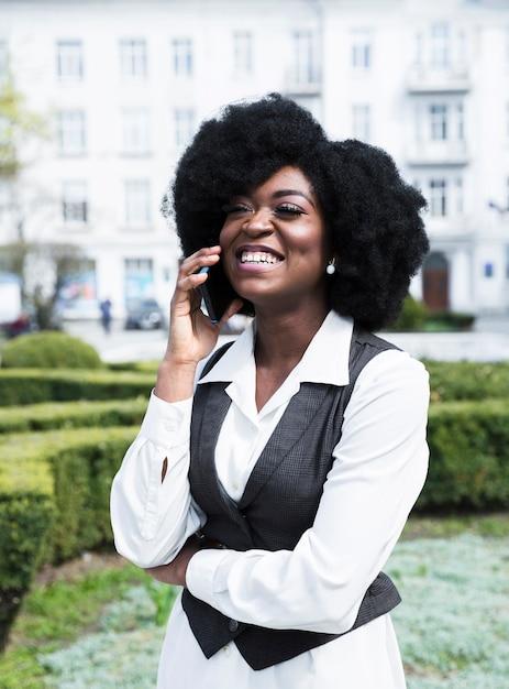 Porträt einer afrikanischen glücklichen jungen geschäftsfrau, die auf smartphone spricht Kostenlose Fotos