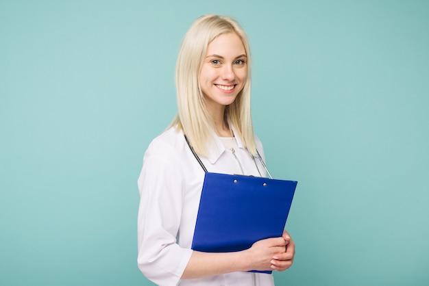 Porträt einer attraktiven jungen ärztin im weißen kittel auf blauem raum Premium Fotos