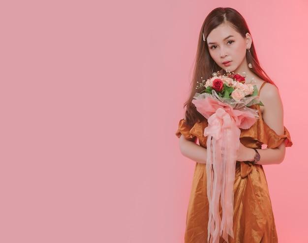 Porträt einer attraktiven jungen frau gekleidet in orange kleid, das blumenstraußblick auf kamera lokalisiert über rosa hintergrund frei von kopienraum gekleidet. asiatisches modell, das mit blumen im studio aufwirft. Premium Fotos
