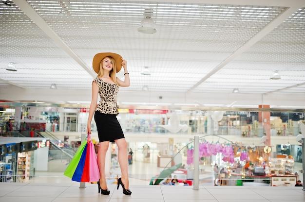 Porträt einer attraktiven jungen frau in der leopardbluse, im schwarzen rock, der mit einem hut aufwirft und in den einkaufstaschen. Premium Fotos