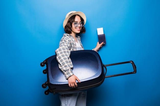 Porträt einer aufgeregten jungen frau, gekleidet in sommerkleidung, die pass mit flugtickets hält, während mit einem koffer isoliert steht Kostenlose Fotos