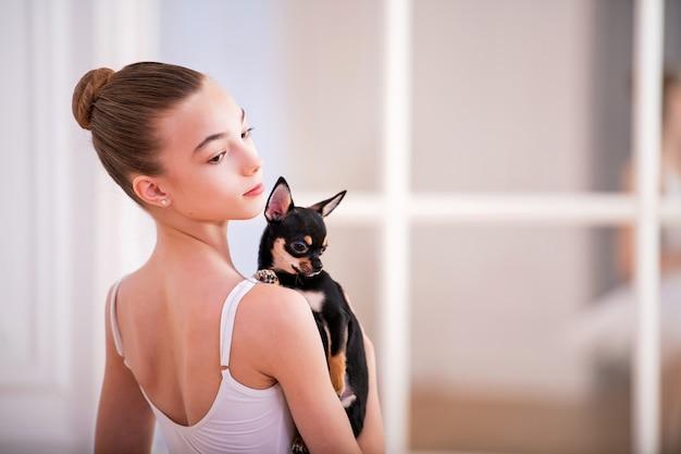 Porträt einer ballerina in weiß mit einem kleinen chihuahua-hund in ihren händen in einem schönen weißen raum vor einem spiegel. Premium Fotos