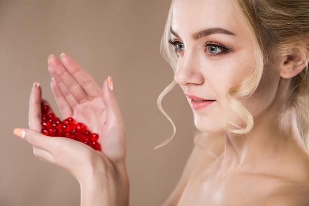 Porträt einer blonden frau mit roten kapseln von vitaminen in ihren händen Premium Fotos