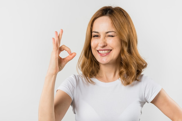 Porträt einer blonden jungen frau, die das okayzeichen macht, das gegen weißen hintergrund blinzelt Kostenlose Fotos