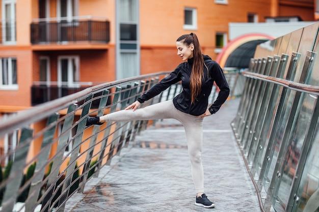 Porträt einer eignungsfrau, die draußen ausdehnende übungen auf treppe tut. Premium Fotos