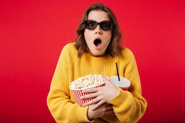 Porträt einer entsetzten frau in der sonnenbrille, die popcorn hält Kostenlose Fotos