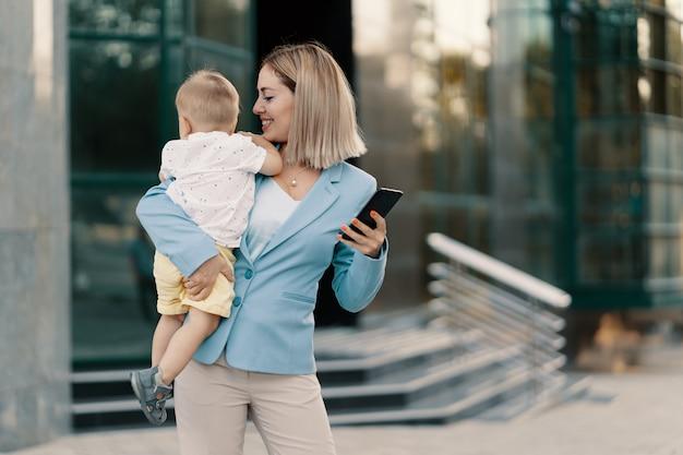 Porträt einer erfolgreichen geschäftsfrau im blauen anzug mit baby Kostenlose Fotos