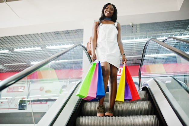 Porträt einer erstaunlichen afroamerikanerfrau mit mehrfarbigen einkaufstaschen auf rolltreppe. Premium Fotos