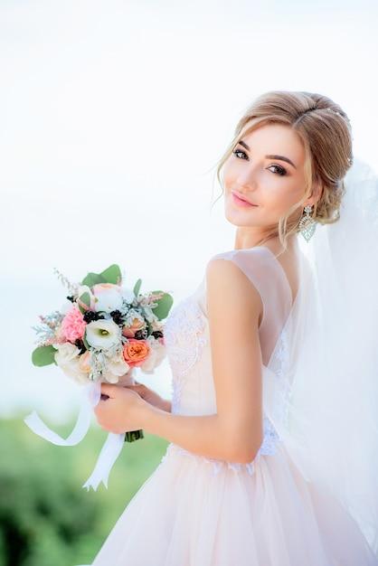 Porträt einer erstaunlichen braut mit dem blonden haar, das pfirsichhochzeitsblumenstrauß in ihren armen hält Kostenlose Fotos