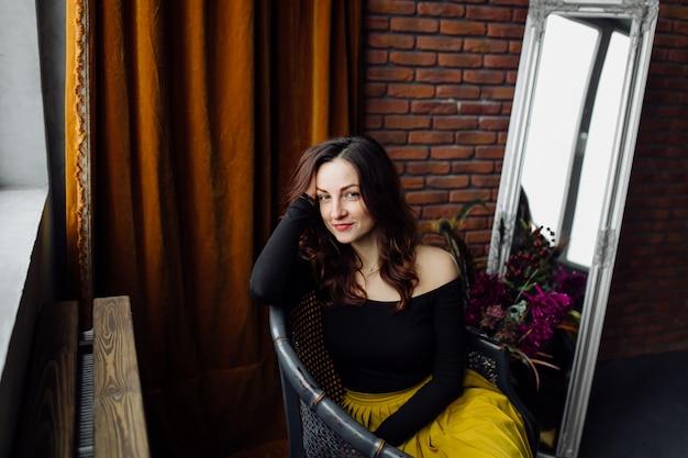 Porträt einer erstaunlichen modernen frau, die in einem stuhl sitzt Kostenlose Fotos