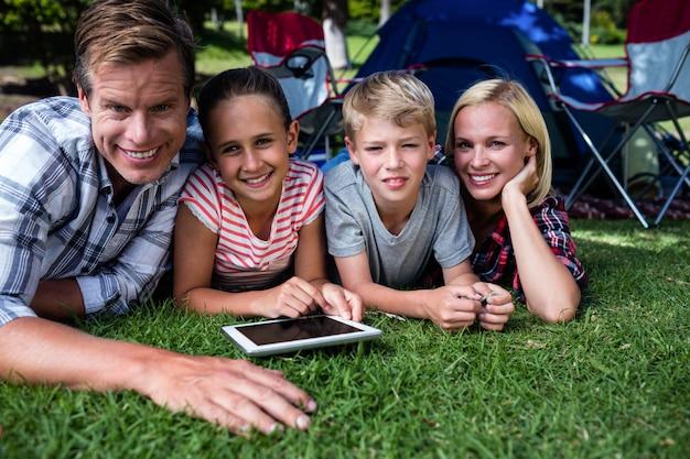 Porträt einer familie, die auf gras liegt und digitale tablette verwendet Premium Fotos