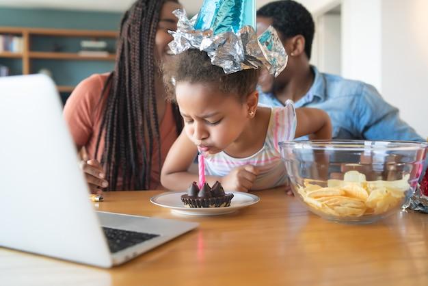 Porträt einer familie, die online geburtstag auf einem videoanruf feiert, während sie zu hause bleibt. Premium Fotos