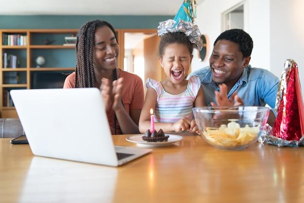 Porträt einer familie, die online geburtstag auf einem videoanruf feiert, während sie zu hause bleibt Premium Fotos