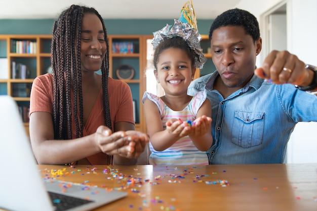 Porträt einer familie, die online geburtstag auf einem videoanruf mit laptop feiert, während zu hause bleiben. Premium Fotos