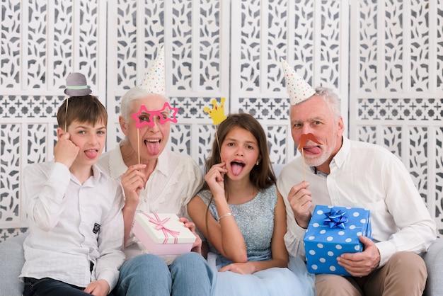 Porträt einer familie, die parteistützen und -geschenkboxen heraus haften zunge hält Kostenlose Fotos
