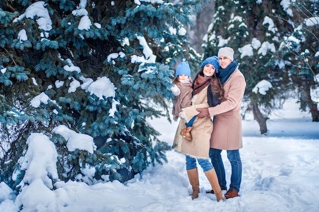 Porträt einer familie im hintergrund der schneebedeckten bäume im wald Premium Fotos