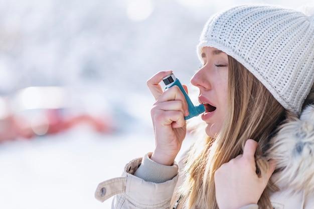 Porträt einer frau, die einen asthma-inhalator in einem kalten winter verwendet Premium Fotos