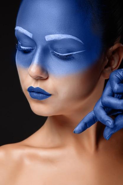 Porträt einer frau, die mit blauer farbe bedeckt ist Kostenlose Fotos