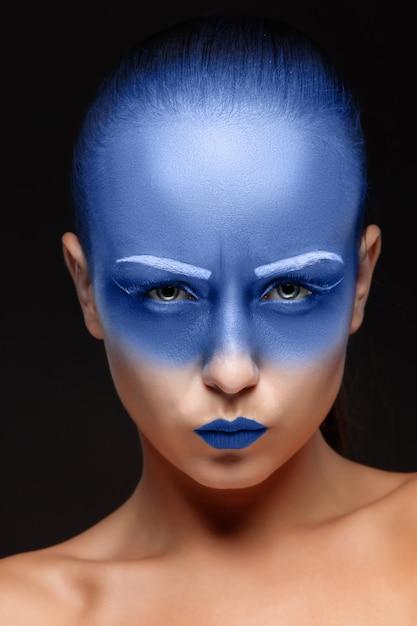 Porträt einer frau, die mit blauer farbe bedeckt posiert Kostenlose Fotos
