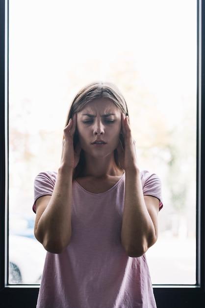 Porträt einer frau, die unter kopfschmerzen leidet Kostenlose Fotos