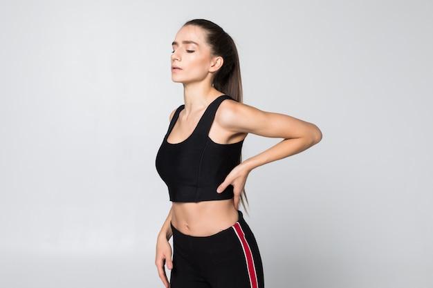 Porträt einer frau in einem fitness-outfit, das nacken-, schulter- und rückenschmerzen lokalisiert auf weißer wand erfährt Kostenlose Fotos