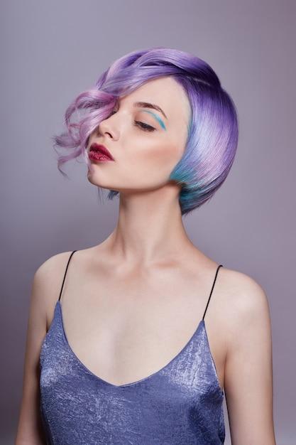 Porträt einer frau mit dem hellen farbigen fliegenhaar, alle schatten von purpur. haarfärbung, schöne lippen und make-up. haare flattern im wind. sexy frau mit kurzen haaren. professionelle färbung Premium Fotos